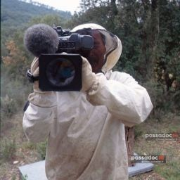 Un homme en tenue d apiculteur tenant une camera de television video - photo André Abbe.jpg